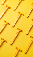 Yellow razor blades on yellow background.