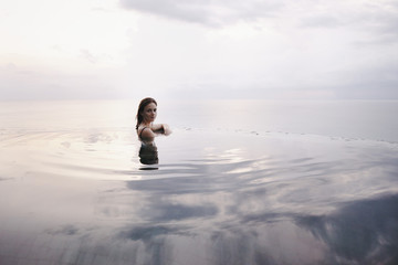 Young attractive woman relaxing in an infinity pool