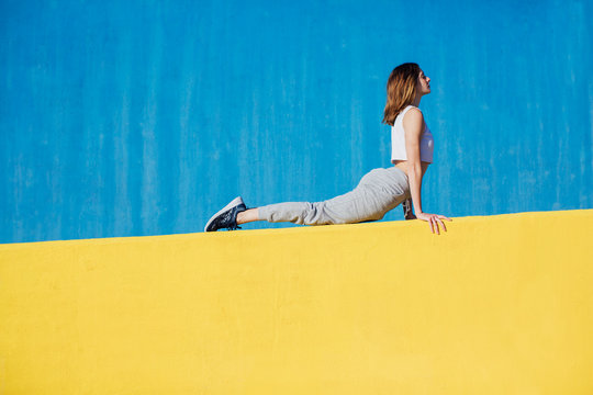 Young ginger woman doing yoga exercises in front of a colorful wall.
