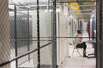 Server room technician sits in a server security cage looking at