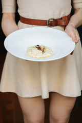 Young woman holding plate of italian truffel risotto