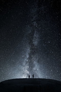 Two Astronauts Explore Landscape Under Milky Way Galaxy