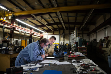 Two male factory workers leaning over digital tablet