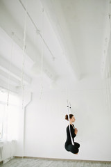 Beautiful girl doing anti gravity aerial yoga exercise in the gym
