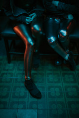 Close up of two women's in shiny tights in the club