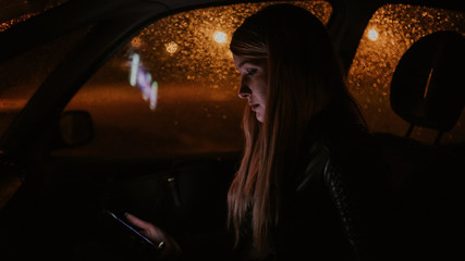 Close up of a beautiful blonde woman in the car at night