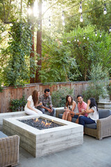 Group of multiethnic millennial friends enjoying drinks by a fire pit in the backyard at home
