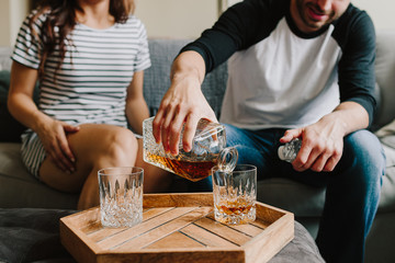 A man and woman sitting on the couch. Pour scotch / whiskey on glasses
