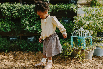 A little girl playing outdoors by a garden