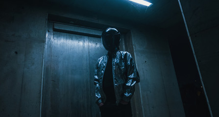Futuristic scene with person with black helmet/mask and silver jacket with neons iluminating around.