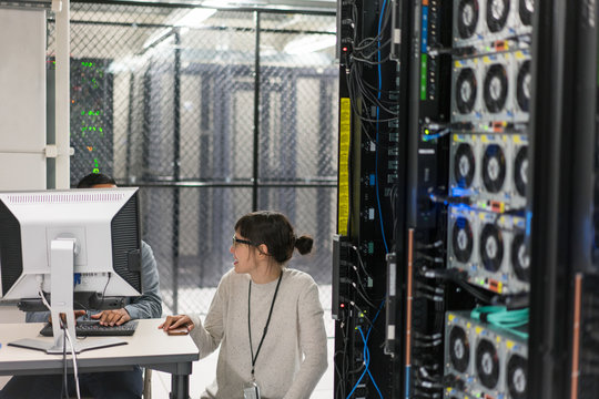 Two technicians talking at a work station in a server room secur