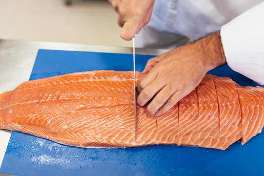 Chef cutting salmon in a professional kitchen
