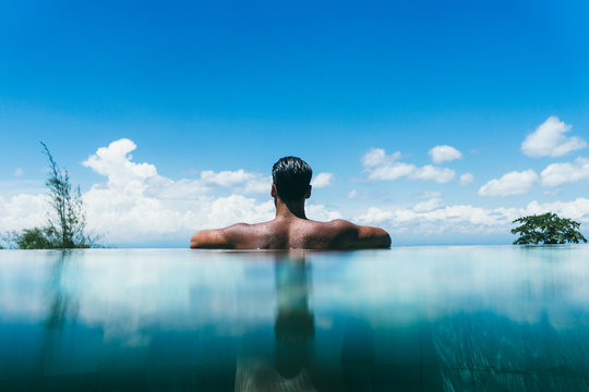 Topless man at infinity pool's edge against sky with fluffy clouds in a hotel
