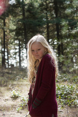 young girl standing in woods