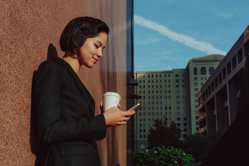 Businesswoman texting on her phone with a coffee