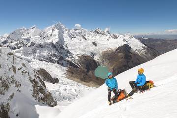 Alpinists resting on the snow with majestic mountains behind him