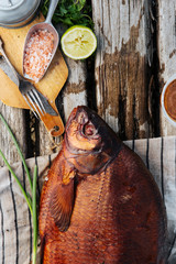Whole smoked fish lying on old wooden boards with lime and salt