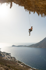 Man rock climber hanging in rope on the blue sky