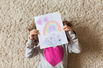 Young girl wearing heart sweater holding a drawing of her family and a rainbow