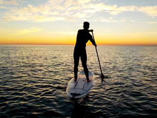Man doing paddle surf at sunrise, Barcelona beach
