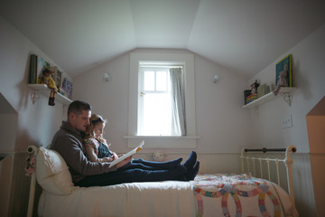 Happy dad and daughter reading together on bed