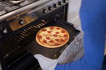 Man putting pizza into oven in kitchen