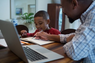 Father helping his son with homework in living room