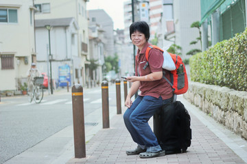 Backpackers woman sit on a suitcase with wheels. Carrying Bag Orange by using a mobile phone while waiting for the next trip.