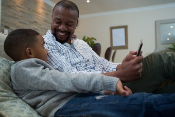 Father and son using mobile phone on sofa in living room