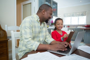 Daughter showing diary to father in kitchen