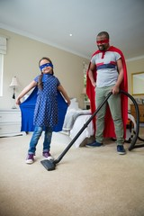 Daughter posing while father cleaning a floor with vacuum