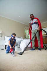 Father and daughter in superhero costume and cleaning a floor