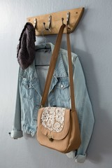 Denim jacket, hat and bag hanging on hook