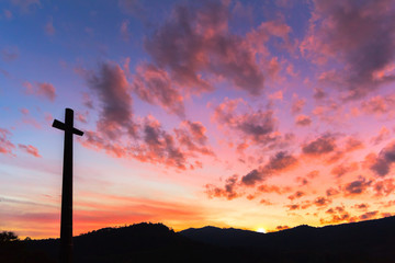 Cross silhouette with the orange from red sunset sky as background.