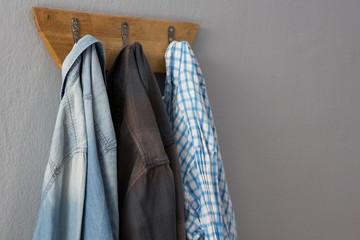 Denim jacket and shirt hanging on hook