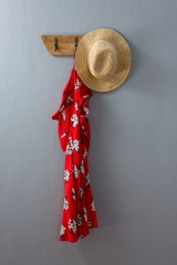 Red dress and hat hanging on hook