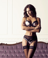 Sexy and beautiful woman in erotic lingerie and stockings posing on a magenta sofa in vintage interior.