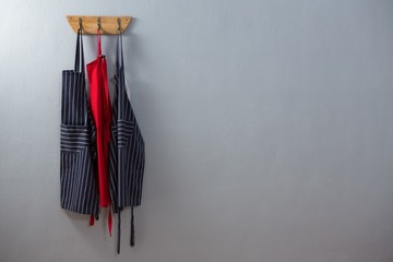 Various aprons hanging on hook