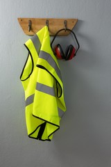 Protective workwear and earmuffs hanging on hook