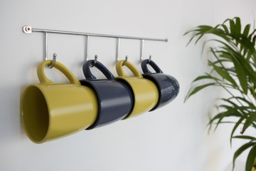 Close-up of colorful mugs hanging on hook