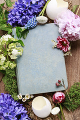 Old book among spring flowers