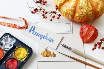 Handwritten word: pumpkin and drawing accessories.