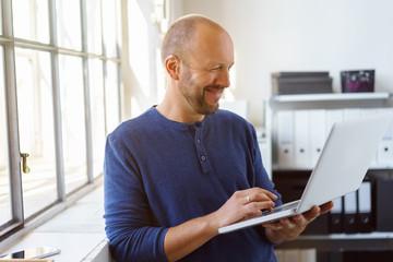 mann im büro schaut lachend auf sein notebook