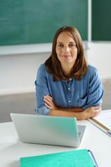 zufriedene lehrerin sitzt am tisch in der klasse und arbeitet am laptop
