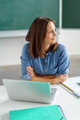 lehrerin in der schule schaut in gedanken zur seite