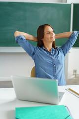 lehrerin sitzt in der klasse und verschränkt entspannt die arme hinter dem kopf