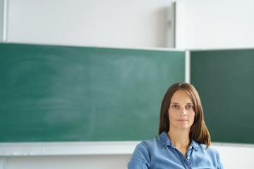 ernste lehrerin vor der tafel im klassenzimmer