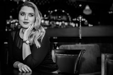 Young elegant plus size woman in cozy atmosphere restaurant. Lady wait on a date in romantic mood. Portrait in deep vintage tones
