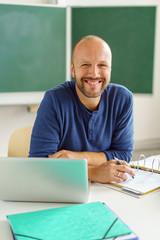 lächelnder lehrer sitzt am tisch im klassenzimmer