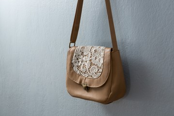 Stylish handbag hanging against wall